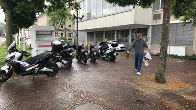 mehrere abgestellte Motorräder, 1 Mann
