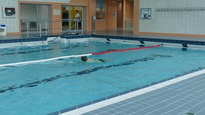 Murganabad: Schwimmer müssen den Abstand einhalten. Am ersten Tag der Wiedereröffnung ist noch wenig los. Schwimmbecken mit einem Schwimmer und Bademeister im Hintergrund.