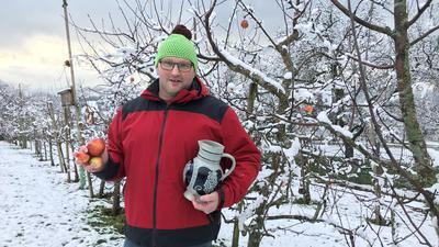 Ein Mann mit Mütze steht inmitten eines Apfelspaliers