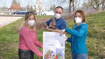 Helfer bringen Hinweisschilder für den Osterweg in Gaggenau an