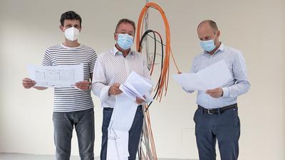 Drei Männer stehen in einem renovierten Raum