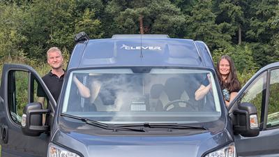 Zwei Leute gucken aus einem Campervan heraus.