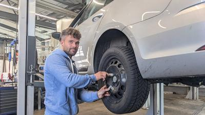 Ein Mann montiert einen Reifen an ein Auto.