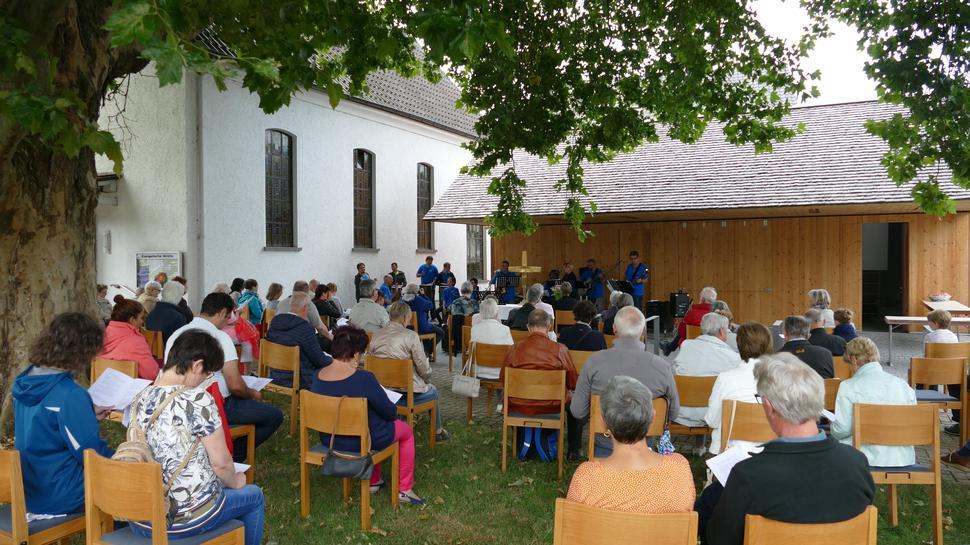 Radfahrerkirche Gaggenau Hörden. Open Air Gottesdienst September 2020. Mehrere Menschen sitzen auf Stühlen auf einer Wiese unter einem Baum.