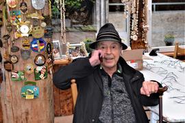 Tony Marshall mit Hut sitzt in der Blockhütte des Mönchhofs und telefoniert