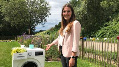 junge Frau vor Waschmaschine