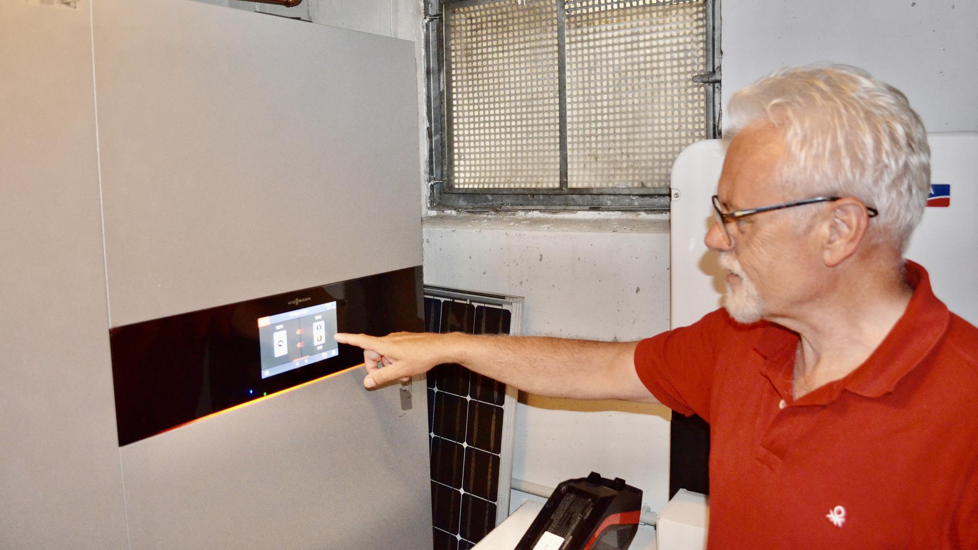 Norbert Gerstner zeigt im Keller auf sein Blockheizkraftwerk