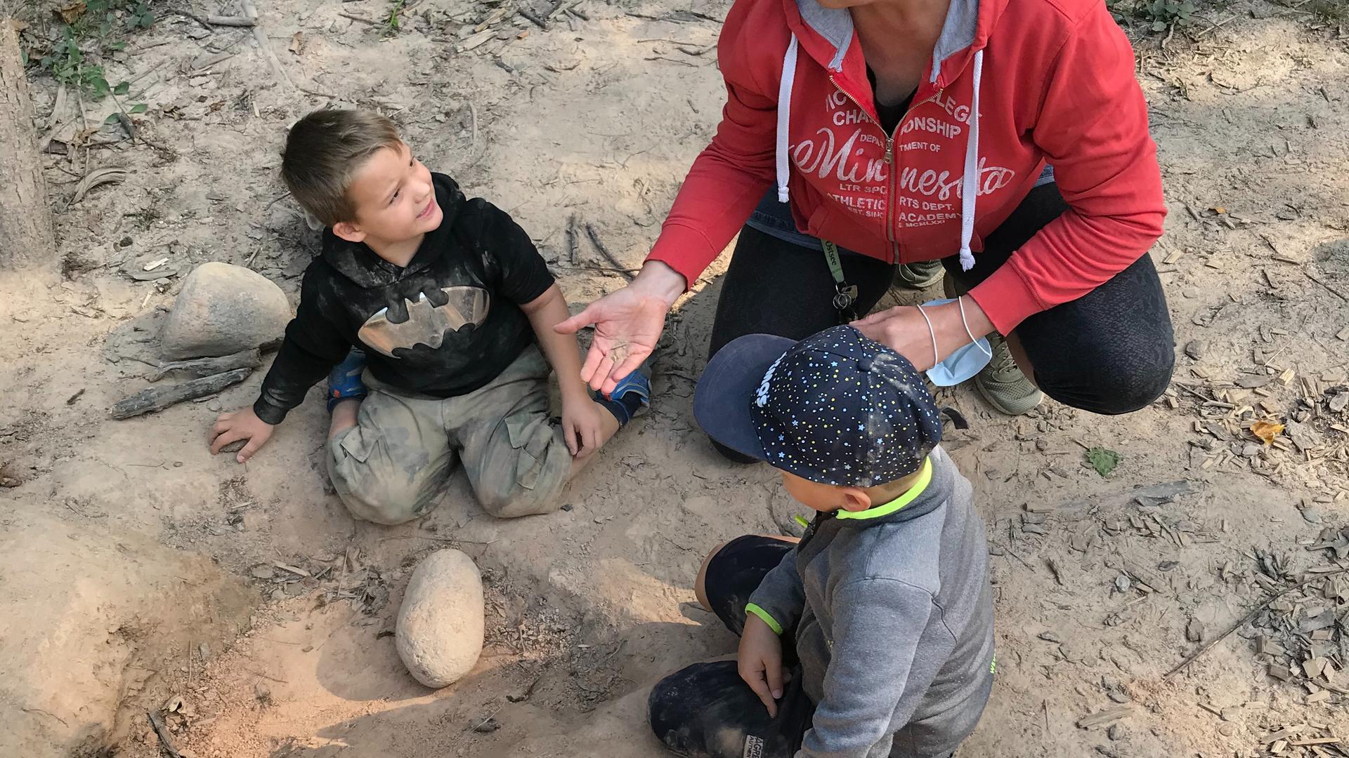 """Kinder werden kreativ: Beim Spiel in der Natur lassen sie ihrer Fantasie freien Lauf. In der Aufnahme begutachtet Andrea Hennersdorf, die Leiterin des Waldkindergartens in Gaggenau, das Baumaterial für ein """"Tierhotel""""."""