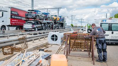 Arbeiter auf Straße, links Autotransporter