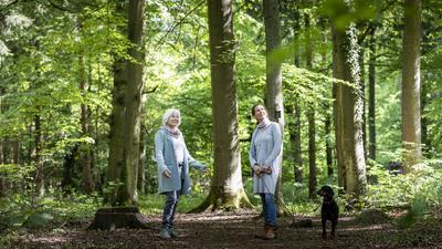 Eine jüngere und eine ältere Frau stehen mit einem Hund in einem Bestattungswald.