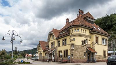 Ein Bahnhofsgebäude und ein Vorplatz.
