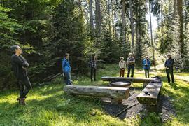 Personen im Wald an einem Platz mit Feuerschale und Bänken
