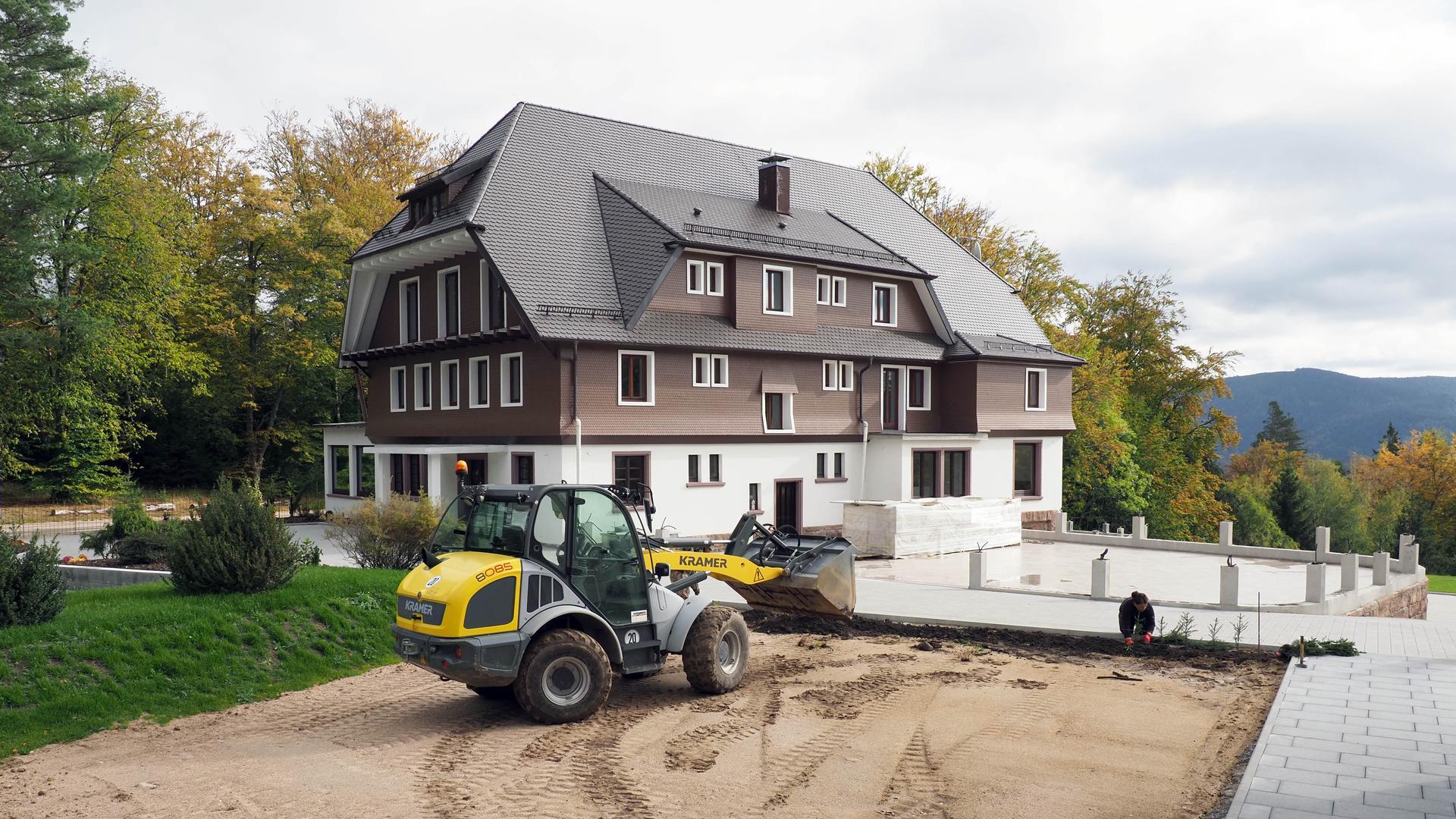 """Die Vorbereitungen laufen: Bauarbeiter planieren auf dem Gelände des Hotels """"Rote Lache"""" in Forbach die Fläche für einen Kinderspielplatz. Am Rand tragen sie Muttererde auf und pflanzen Fichtensetzlinge ein."""