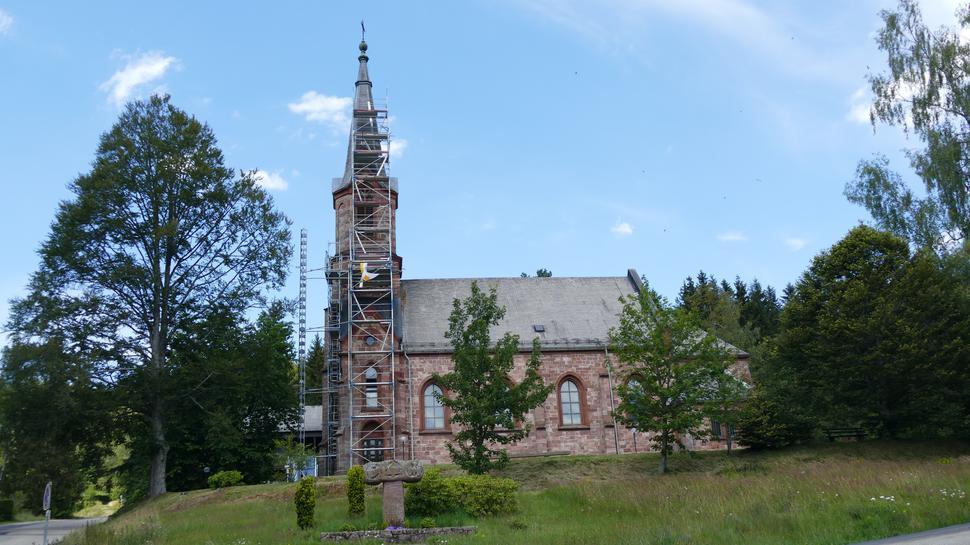 Pfarrkirche Herrenwies, Seitenansicht mit Baum, Baugerüst und Gedenkstein