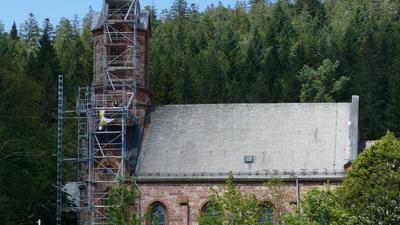 seitliche Ansicht einer Kirche mit Baugerüst am Kirchturm