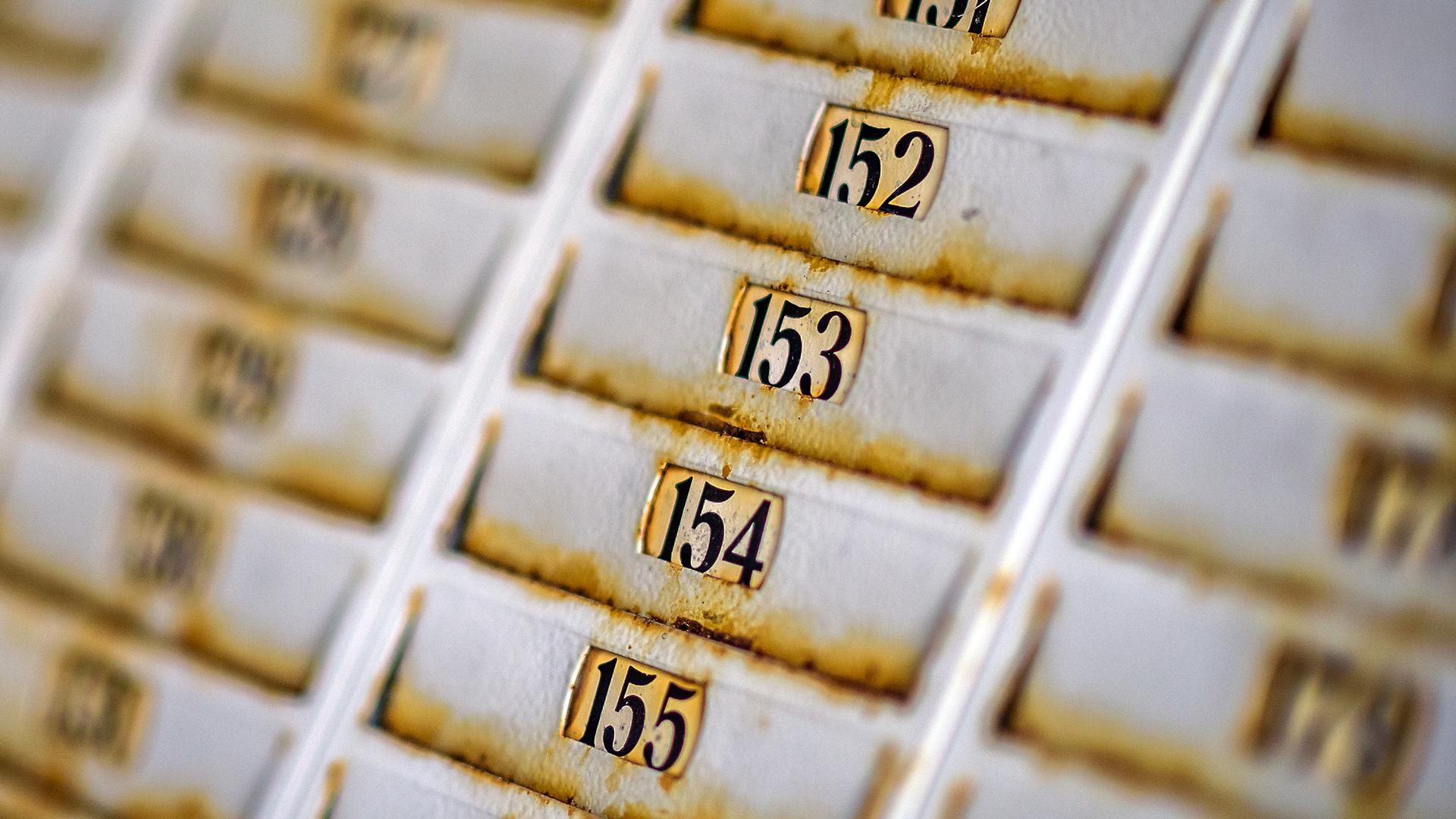 Stempelkartenregal mit alten rostigen und nummerierten Fächern in der ehemaligen Weisenbach-Papierfabrik (ehemals Papierfabrik Holtzmann)