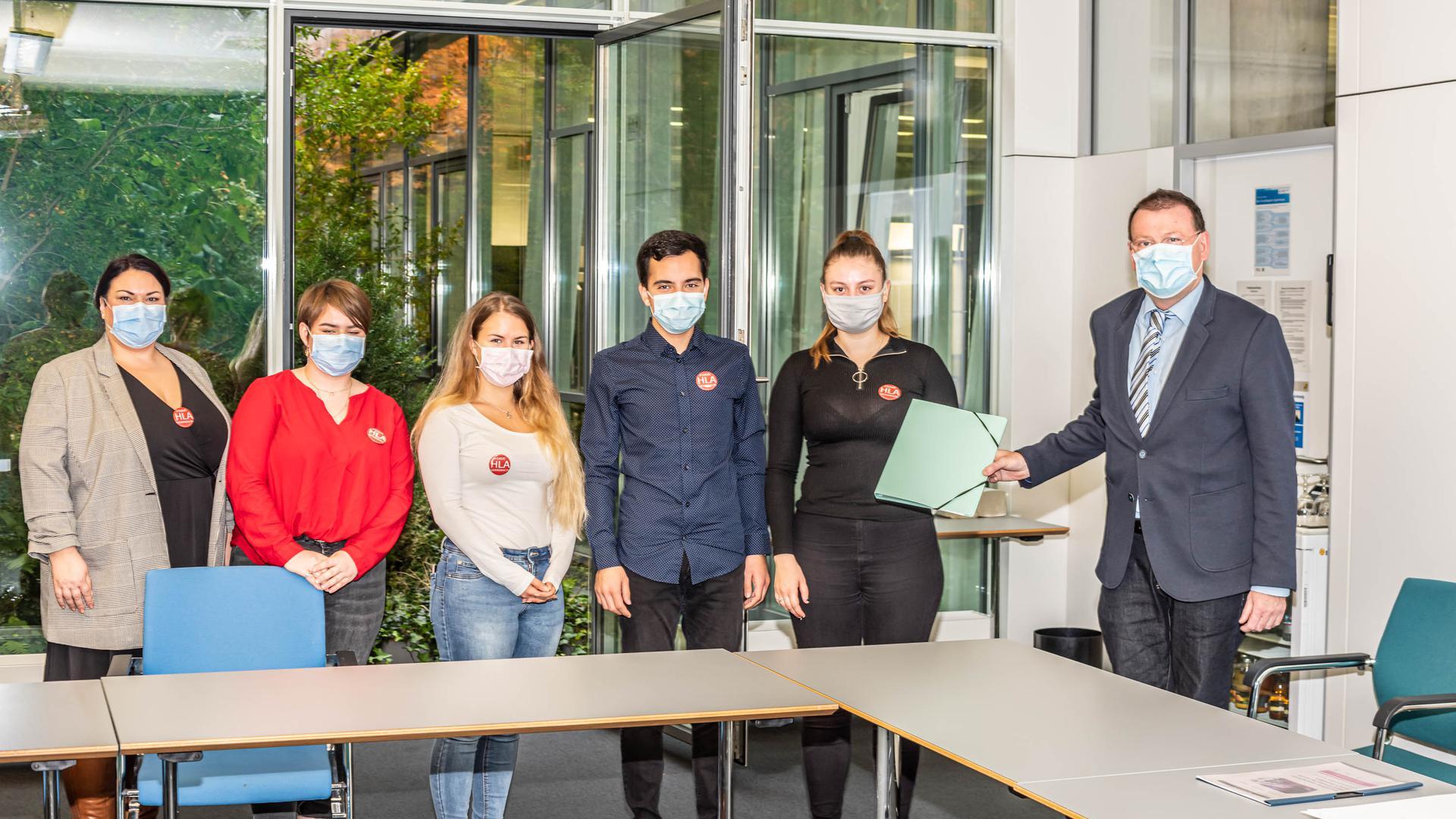 Die Elternvertreterin und Schülerinnen und Schüler der HLA übergeben dem Ersten Landesbeamte. Dr. Jörg Peter die Mappen mit den Unterschriften (von links).