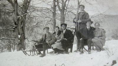 Historische Aufnahme von 1930: Zwei Schlitten mit zwei bzw. drei Personen und eine Person in der Mitte stehend mit Skiern auf einer Rodelstrecke auf dem Buchholzweg