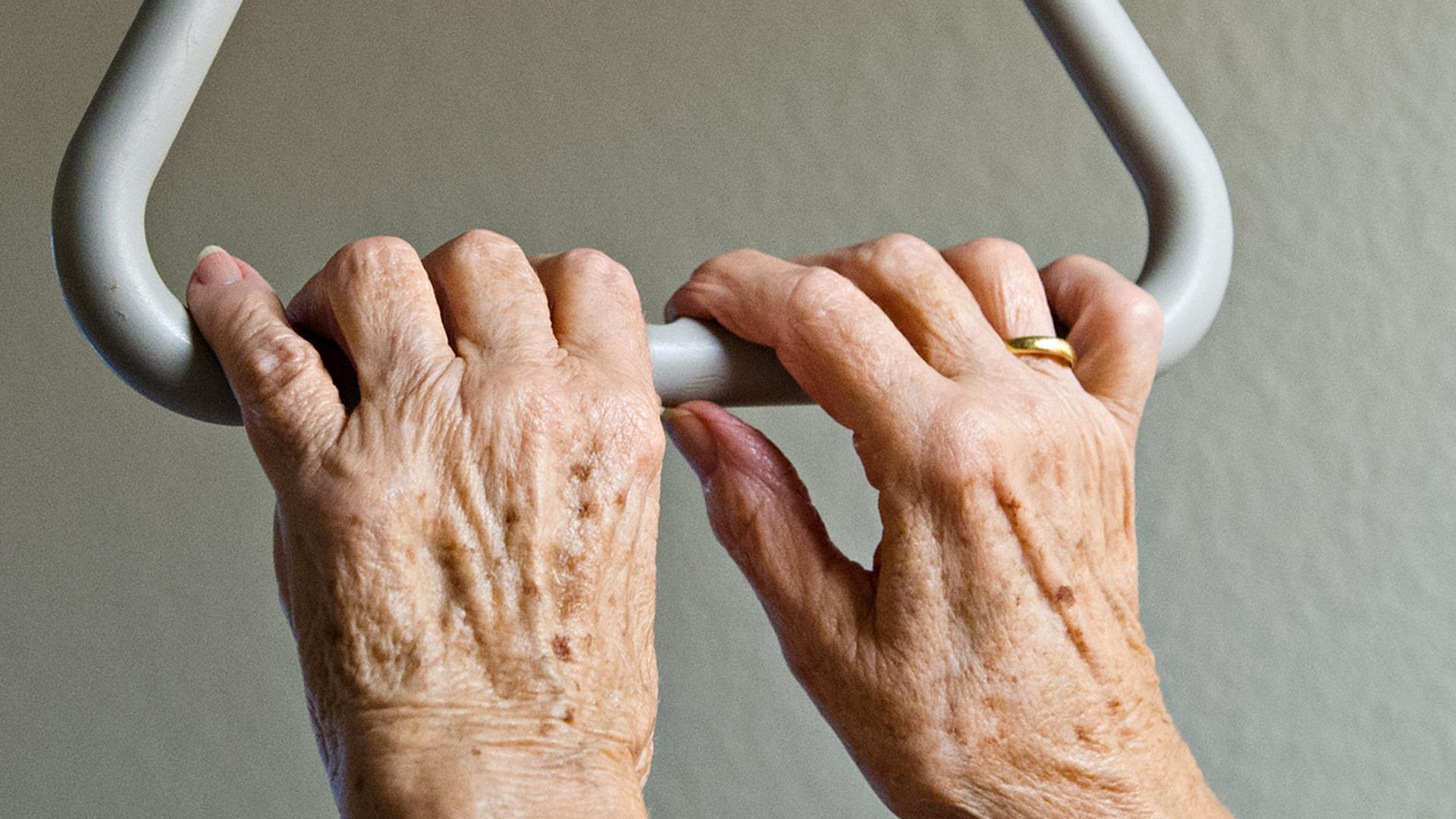 ARCHIV - ILLUSTRATION - Eine Bewohnerin einer Krankenwohnung hält sich am 06.09.2013 in Stuttgart (Baden-Württemberg) an ihrem Bett an einem Haltegriff fest. Die Gewerkschaft Verdi fordert mehr Personal in der Altenpflege. (zu dpa vom 30.10.2017) Foto: Daniel Bockwoldt/dpa +++ dpa-Bildfunk +++