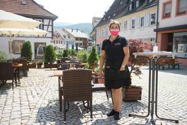 Eine Frau steht vor mehreren Tischen und Stühlen.