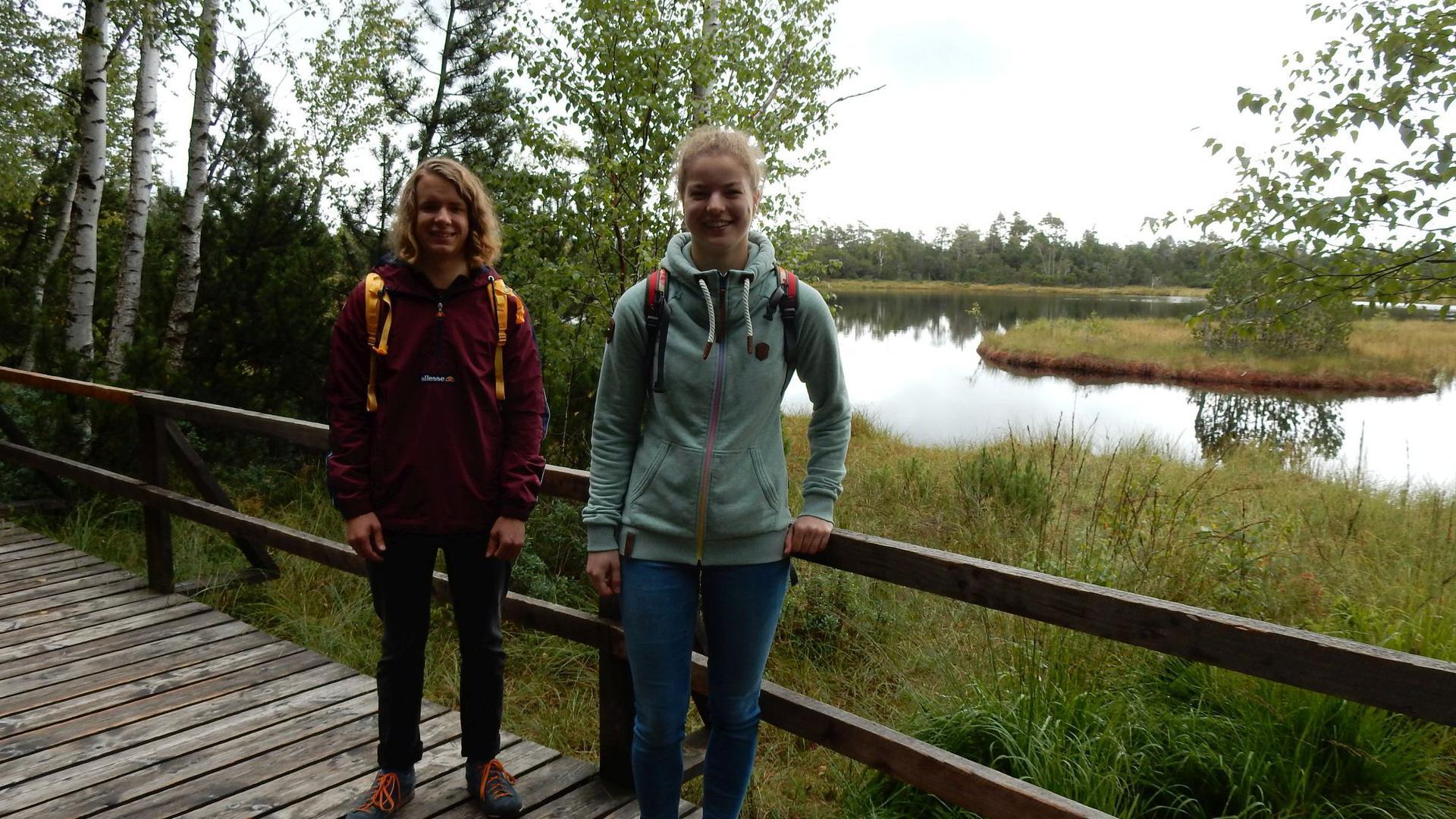 Elischa Mannal (links) und Anna Sinke in Wanderkleidung auf dem Bohlenweg am See im Hochmoorgebiet Kaltenbronn