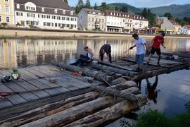 Vier Männer arbeiten an einem Floß auf der Murg in Gernsbach