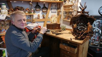 Markus Schleicher sitzt an der Werkbank seines Urgroßvaters. Auf der Werkbank liegen eine traditionelle Kuckucksuhr aus Holz und eine Schwarzwälder Schilduhr.