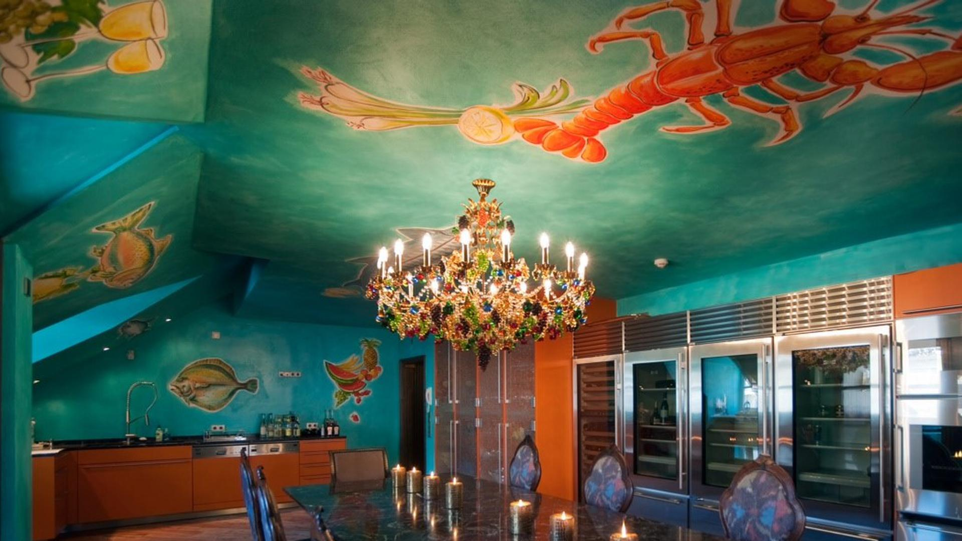 Großer Raum mit zum Esszimmer hin offener Küche. Die Wände und die Decke sind mit Fischen und einem Hummer bemalt vor einem türkis-blauen Hintergrund.