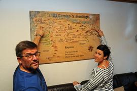 Heike und Marco Borchard zeigen in ihrem Wohnzimmer auf eine Karte, die den Jakobsweg abbildet
