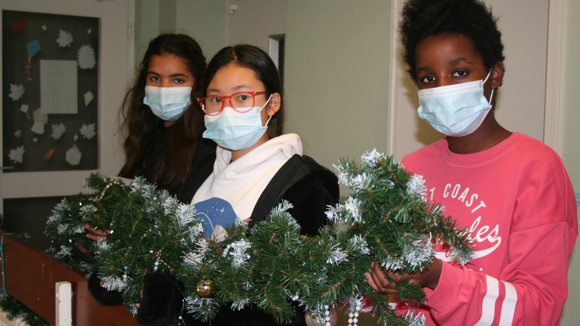 Drei Mädchen halten gemeinsam eine weihnachtlich dekorierte Tannengirlande