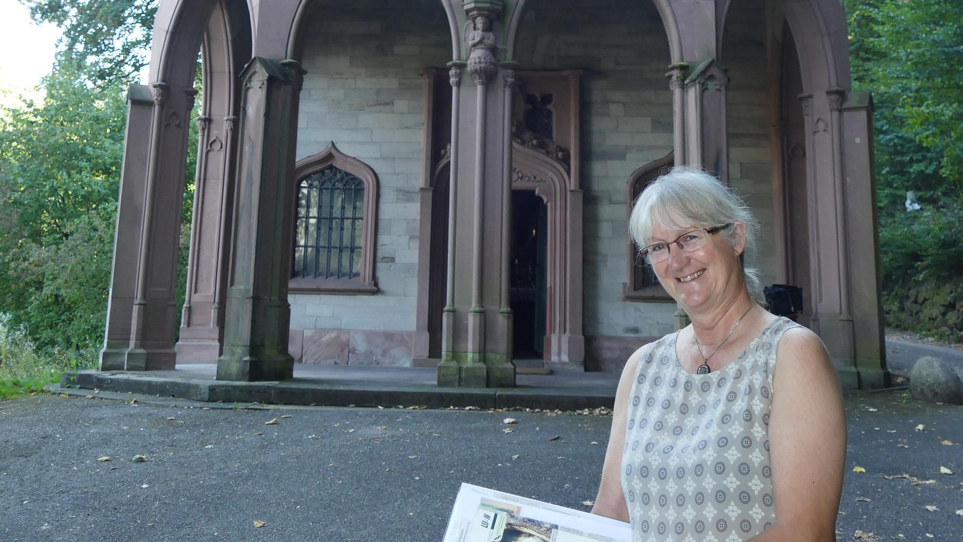 Frau vor einer Kapelle, mit einem Buch in den Händen