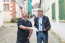 Zwei Männer stehen in einer Straße.