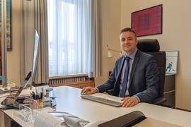 Ein Mann sitzt an seinem Schreibtisch.