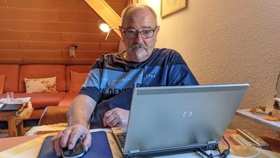 Ein Mann sitzt vor seinem Laptop.