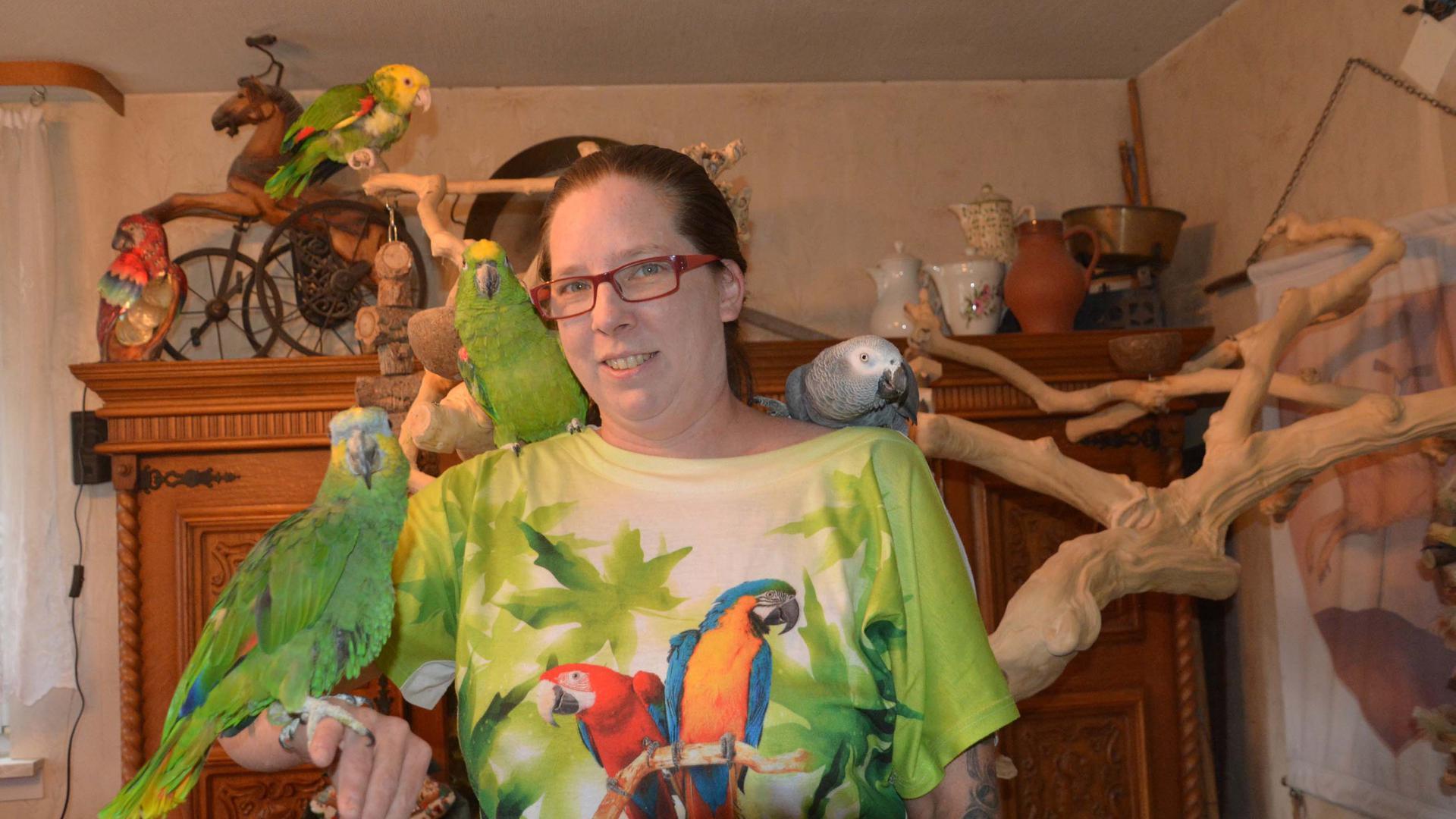 Frau mit mehreren Papageien auf Arm und Schulter
