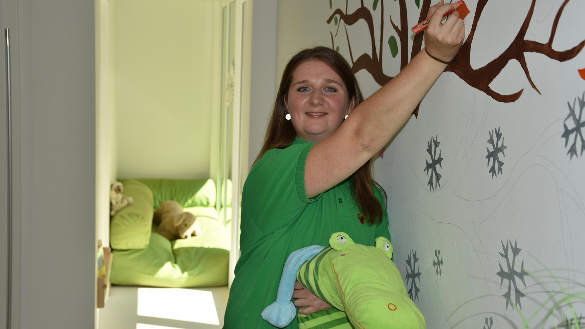 Kindergarten Spielwiese: Pia Wiggenhauser, Einrichtungsleiterin der neueröffneten Kinderkrippe der Stadt Gernsbach unter der Trägerschaft der Spielwiese - am Vierjahres-Geburtstagsbaum für die Kinder, an dem die Eltern noch mitgestalten dürfen