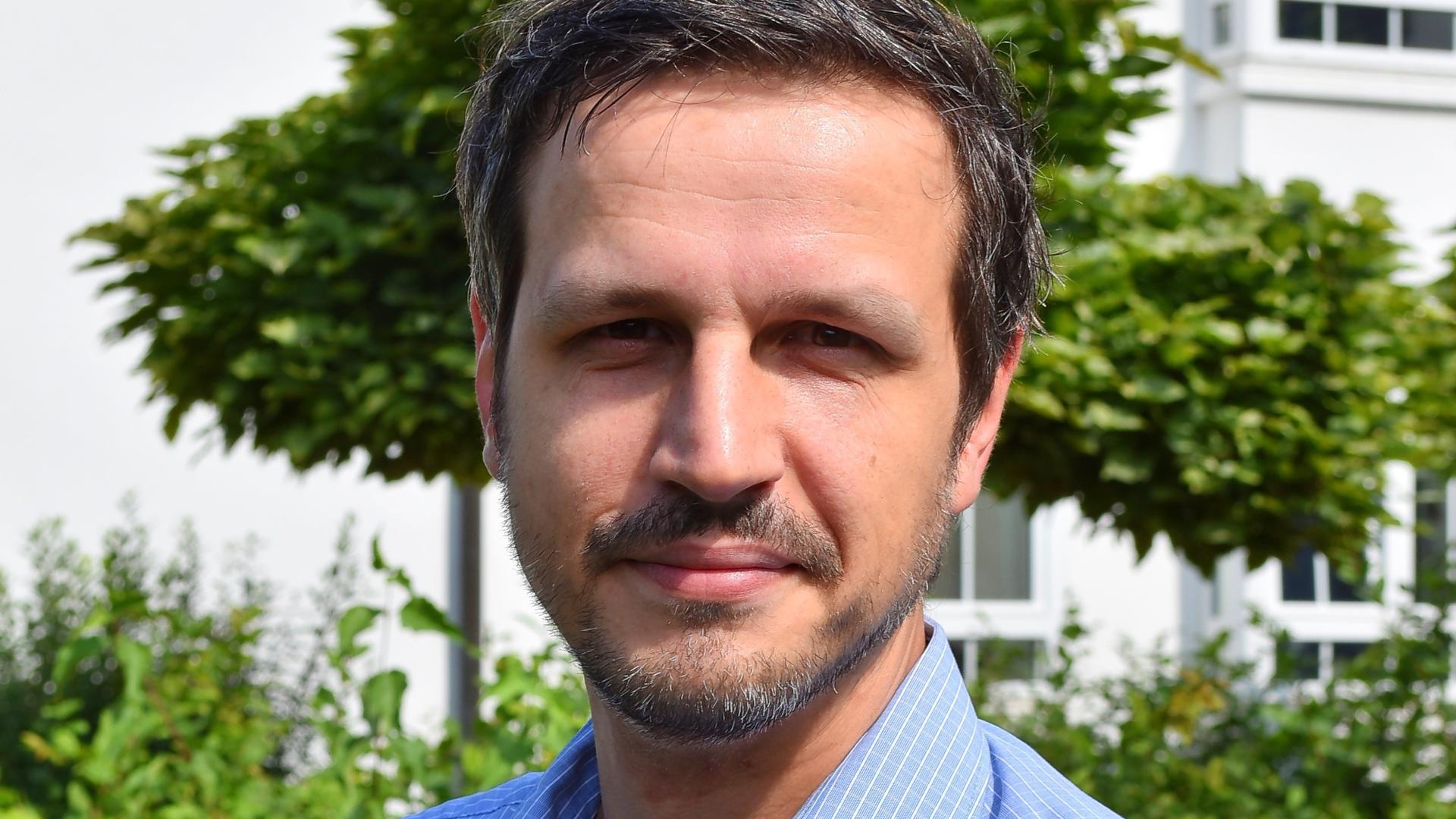 Mann mit Bart vor weißem Haus