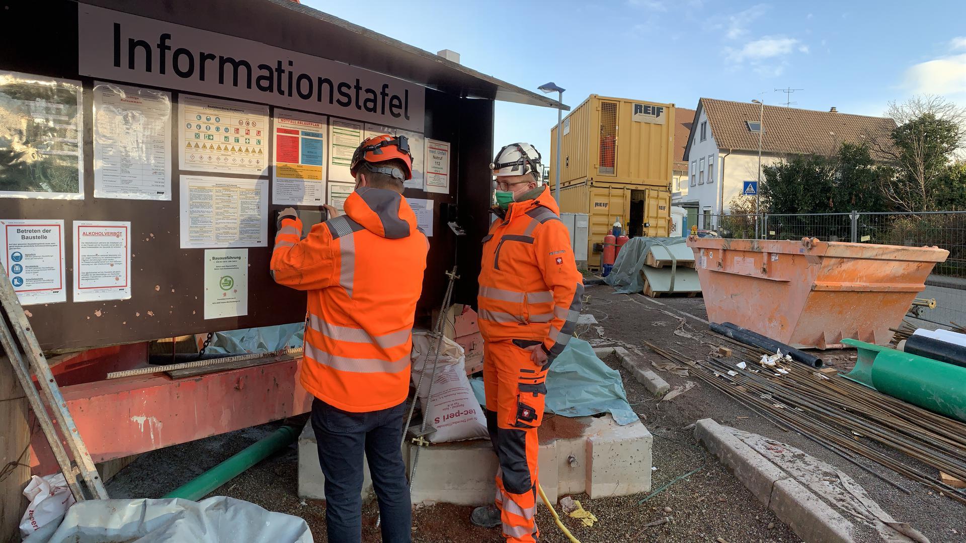 """Sicherheit muss gewährleistet sein. Dennis Saldern (links) und Tobias Künstel tragen sich in die """"Anwesenheitsliste"""" ein. Im Hintergrund sind die Schalelemente für den Endausbau des Stollens am Bahnhof zu sehen."""