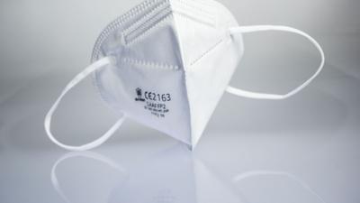 Eine FFP2-Maske liegt auf einem Leuchttisch.