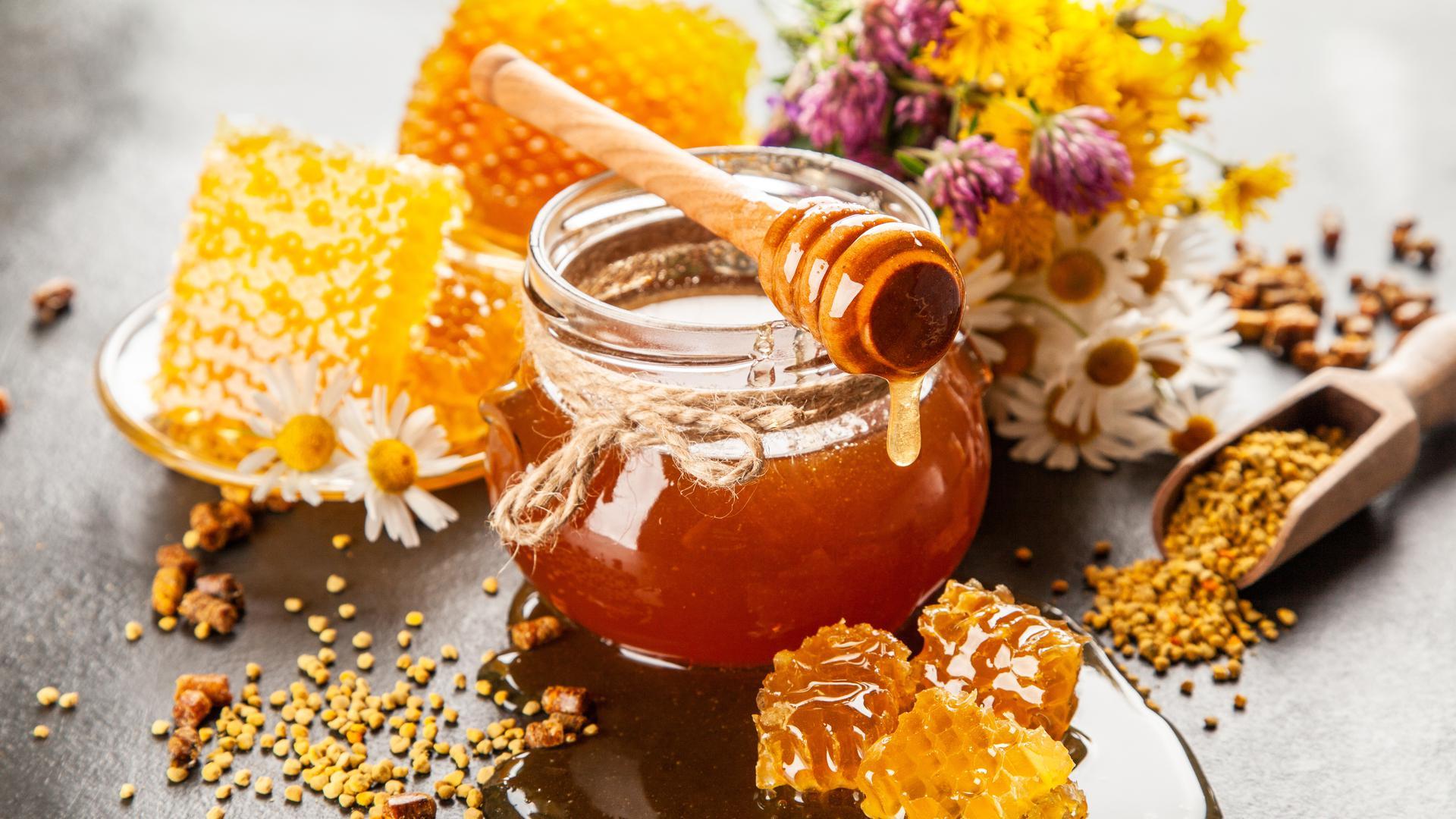 Ein Glas Honig und Bienenwaben stehen auf einem Tisch.
