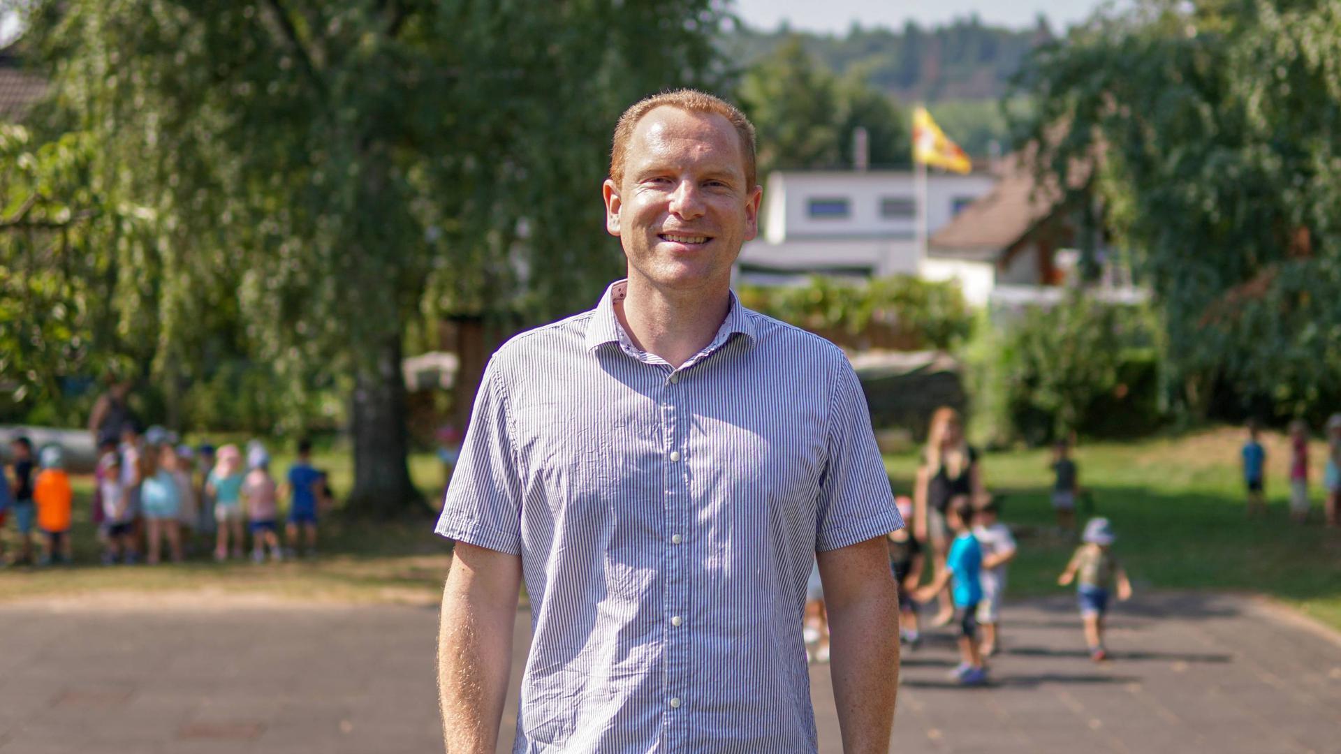 Pädagogische Arbeit im Freien: Rings um Adrian Groll herum toben die Kinder. Der Erzieher ist zurzeit noch mit organisatorischen Dingen beschäftigt, wird demnächst aber selbst in den Gruppen mitarbeiten.