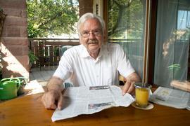 Ein Mann mit einer Zeitung in der Hand.