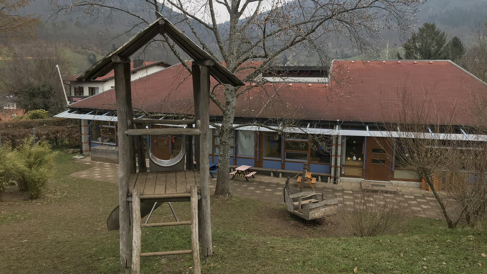 Ein Kindergarten mit einem Spielplatz davor.