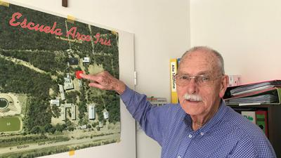 Ein Mann steht vor einem Plakat