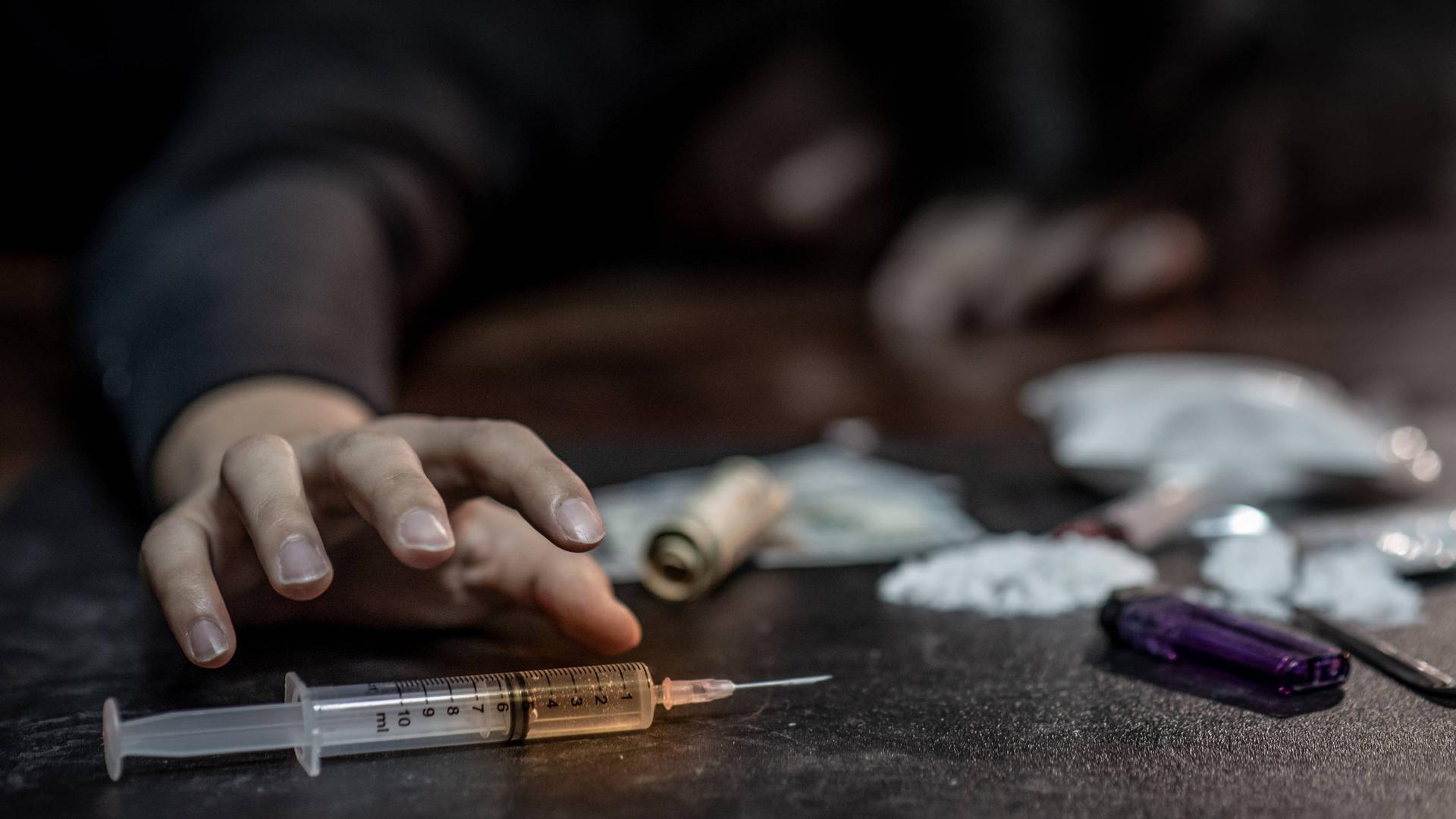 Symbolfoto zum Thema Drogen Sucht Spritze Süchtig Kokain Heroin . Fotobeschreibung: Male junkie hand trying to grab injection syringe of cooked heroine. Hard drug overdose and addiction concept.