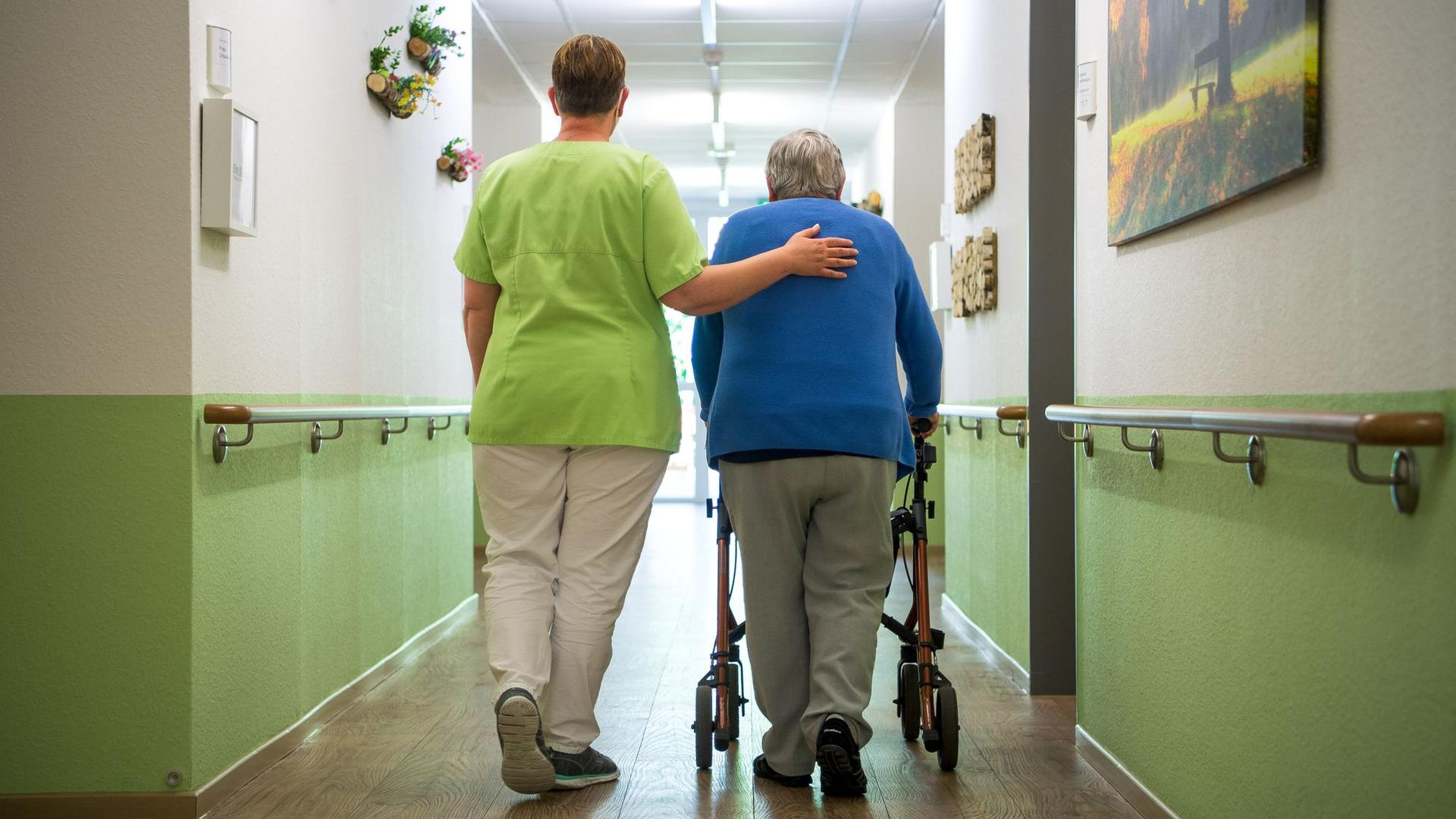 """Eine Pflegefachkraft geht mit einer Bewohnerin durch das Seniorenheim """"Mein Zuhause Nienburg""""."""