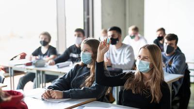 Schüler büffeln an einem Gymnasium mit Maske.