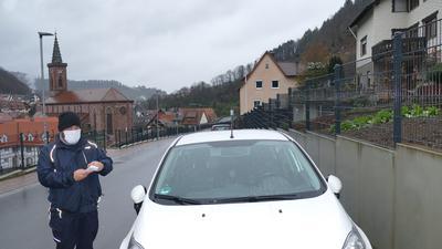 Alexander Preis, Mitarbeiter des Gemeindevollzugsdienst, steht in Weisenbach auf der Straße neben einem weißen Auto, das entgegen der Fahrtrichtung parkt.