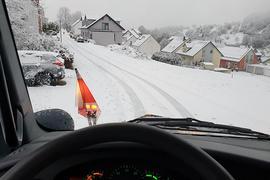Blick aus einem Räumfahrzeug auf ein verschneites Dorf.