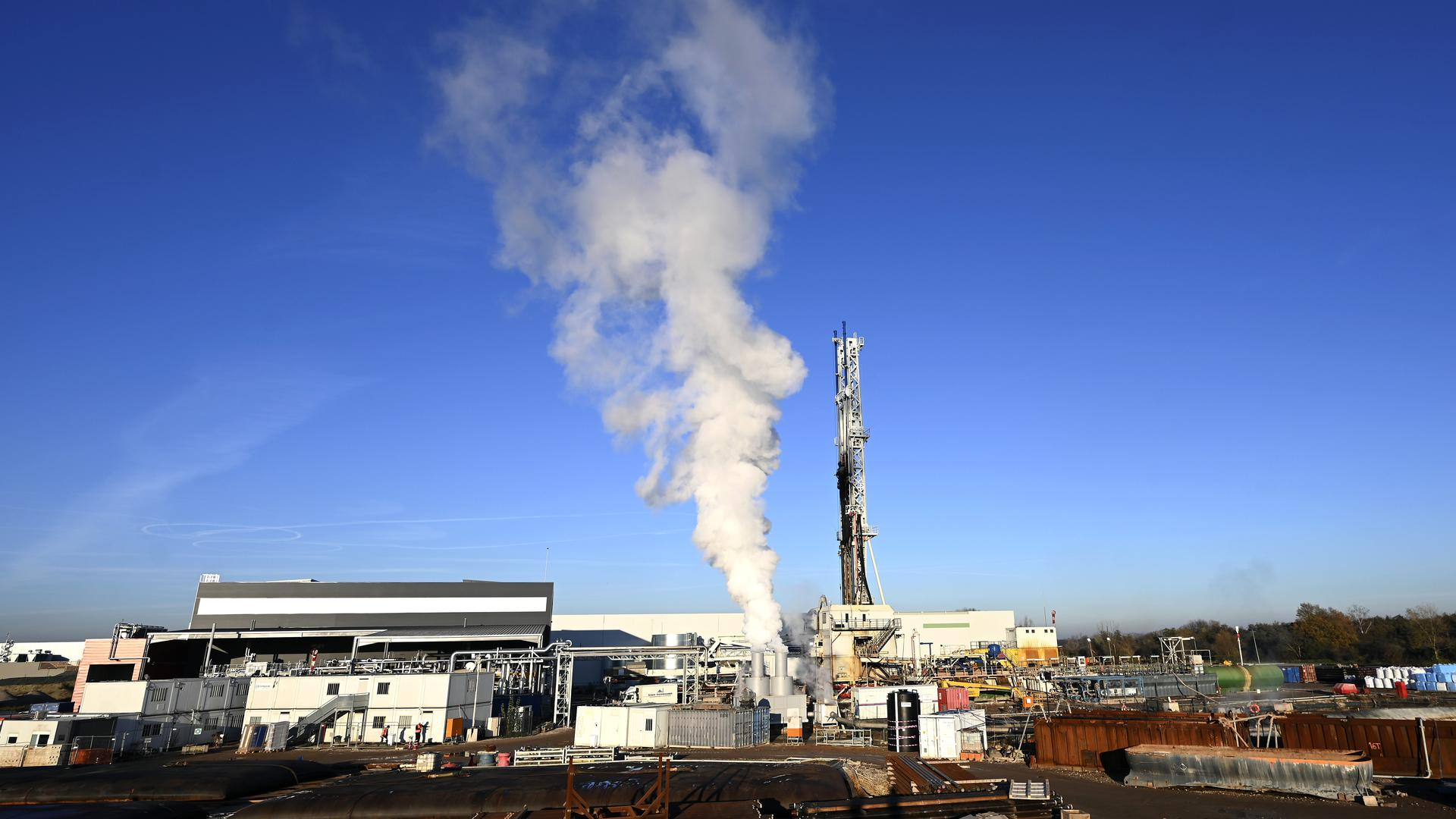 Blick auf das Geothermie-Kraftwerk, von dem Dampf aufsteigt.